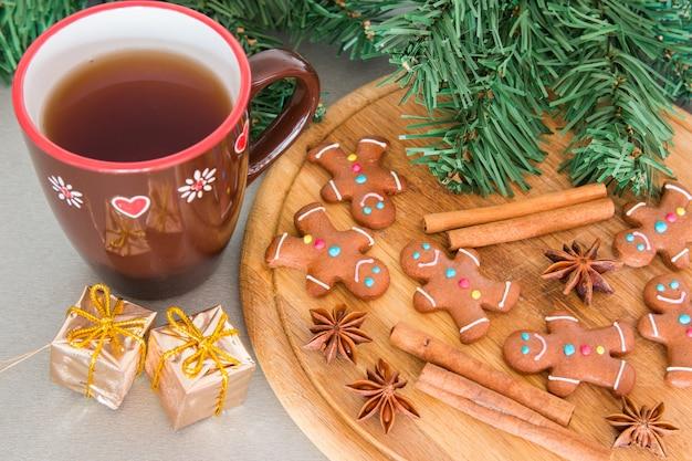 Muitos homenzinhos de gengibre em uma tábua de madeira e chá Foto Premium