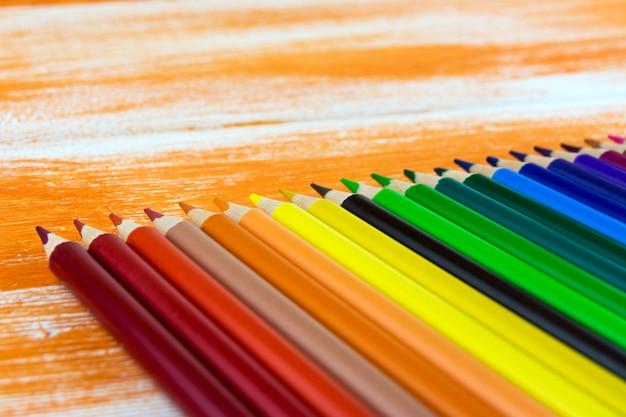 Muitos lápis de cor deitado sobre uma placa laranja Foto Premium
