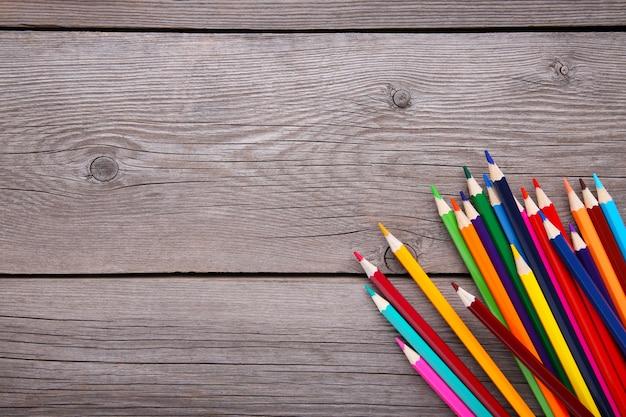 Muitos lápis de cor diferentes em cinza de madeira Foto Premium