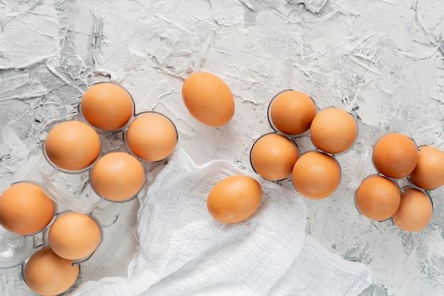Muitos ovos crus de frango cru em uma bandeja de plástico na mesa de grunge, dietas especiais de ovo Foto Premium