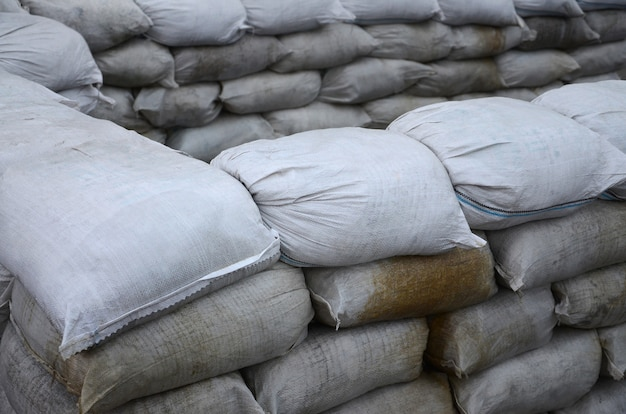 Muitos sacos de areia sujos para defesa contra inundações. barricada protetora de sacos de areia para uso militar. belo bunker tático Foto Premium