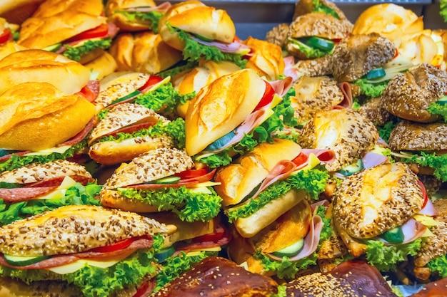 Muitos sanduíches em uma vitrine de uma lanchonete cozinhando à venda. Foto Premium