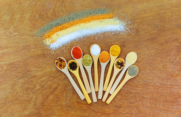 Muitos tipos diferentes de especiarias da ásia. colheres de madeira bonitas com opinião superior das especiarias. Foto Premium