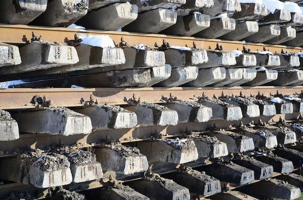 Muitos trilhos velhos e dormentes são empilhados em um armazém railway no inverno. Foto Premium