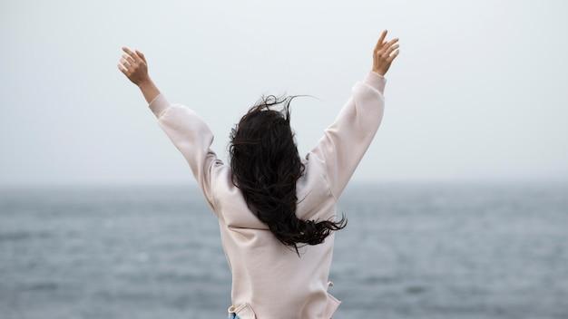Mulher à beira-mar com os braços levantados Foto gratuita