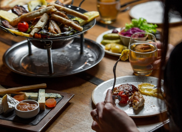 Mulher a jantar ao redor da mesa doada com comida Foto gratuita