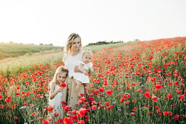 Mulher abraça suas duas filhas entre o campo de papoulas Foto gratuita