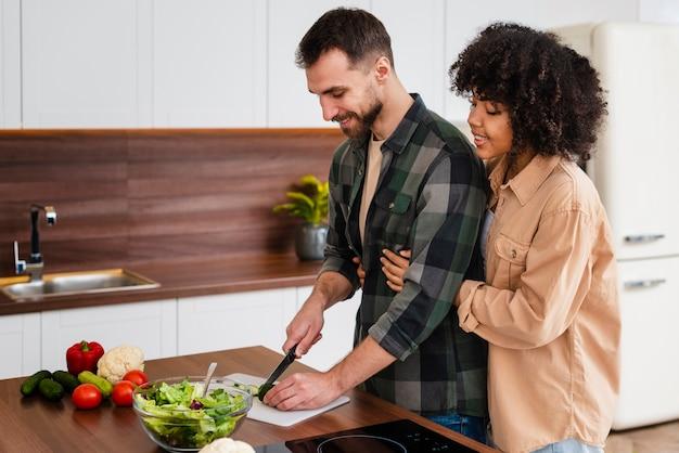 Mulher, abraçando, homem, cozinhar Foto gratuita