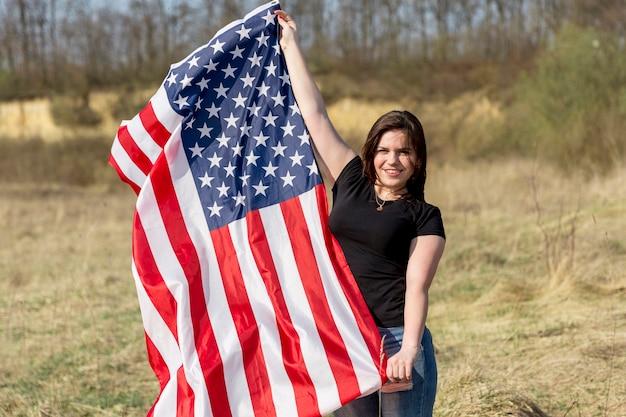 Mulher acenando a bandeira dos eua fora durante o dia da independência Foto gratuita