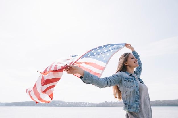 Mulher acenando grande bandeira dos eua Foto gratuita
