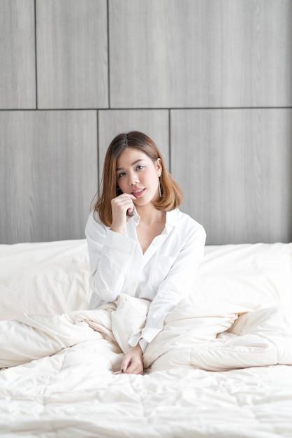 Mulher acorda na cama Foto Premium