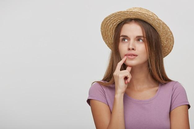 Mulher adolescente com um chapéu de palha e uma fita rosa olha para o lado intrigada, tentando se lembrar de algo importante Foto gratuita