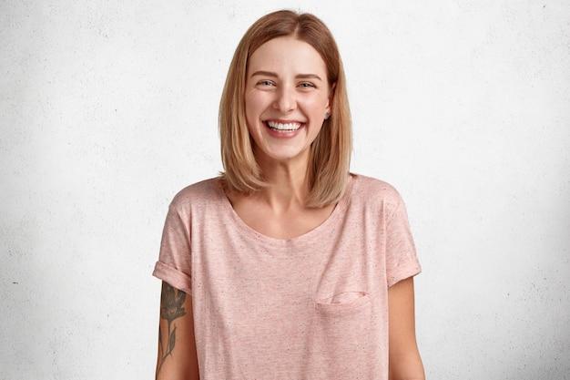 Mulher adorável e feliz com um sorriso largo e cheio de dentes brancos, usa uma camiseta casual grande demais, tem uma tatuagem, um visual simpático atraente Foto gratuita