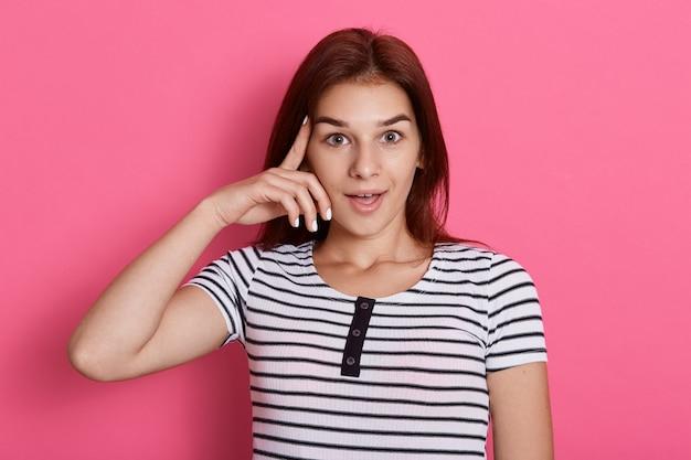 Mulher adorável mantém os dedos indicadores na têmpora, tenta se reunir com os pensamentos, vestida com uma camiseta listrada casual, isolada sobre a parede de rosas, tem uma ideia, parece animada. Foto gratuita