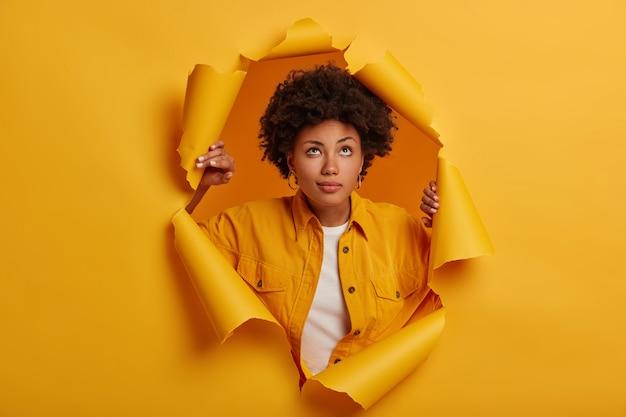 Mulher adorável pensativa olhando para cima, parada em um buraco de papel rasgado, vestida com roupa da moda, pensando em algo Foto gratuita