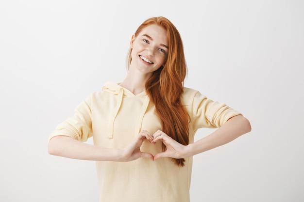 Mulher adorável redead mostrando gesto de coração e sorrindo Foto gratuita