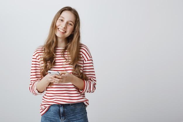 Mulher adorável sorrindo feliz e usando smartphone Foto gratuita