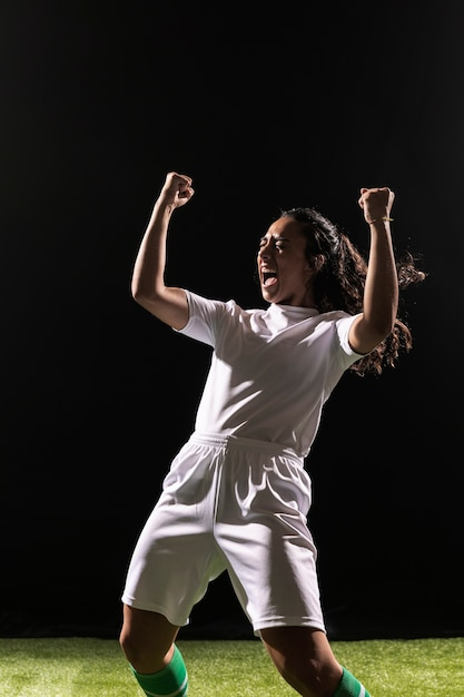 Mulher adulta no sportswear comemorando Foto gratuita