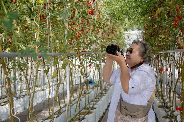 Mulher adulta que toma a foto na jardinagem. prolongar a mulher de aposentadoria ativa para fazer atividades Foto Premium