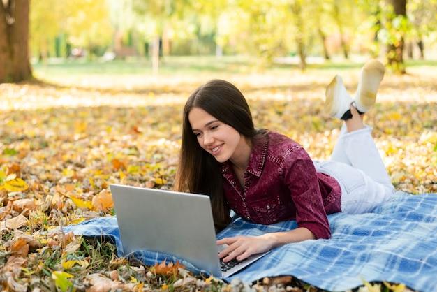 Mulher adulta trabalhando no laptop ao ar livre Foto gratuita