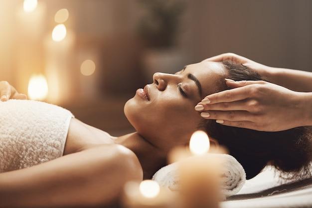 Mulher africana atraente, desfrutando de massagem de rosto no salão spa. Foto gratuita
