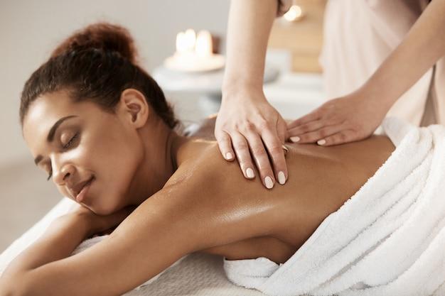Mulher africana atraente tendo massagem relaxante no salão spa. olhos fechados. Foto gratuita