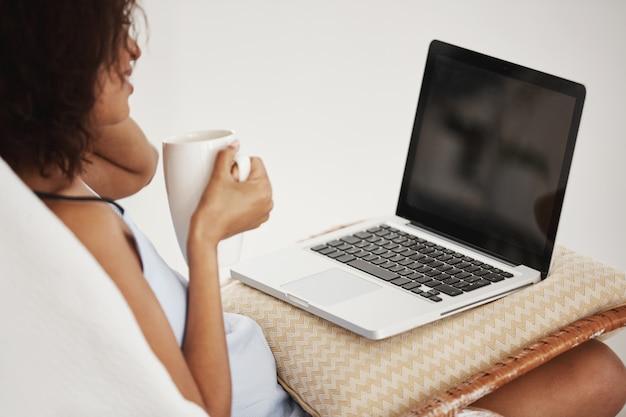 Mulher africana atrativa que sorri guardando o copo que olha o portátil que senta-se na cadeira em casa. Foto gratuita