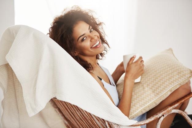 Mulher africana bonita em roupa de noite que sorri guardando o copo que senta-se na cadeira em casa. Foto gratuita