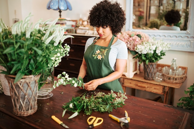 Mulher africana, classificando as plantas de flor na mesa de madeira Foto gratuita