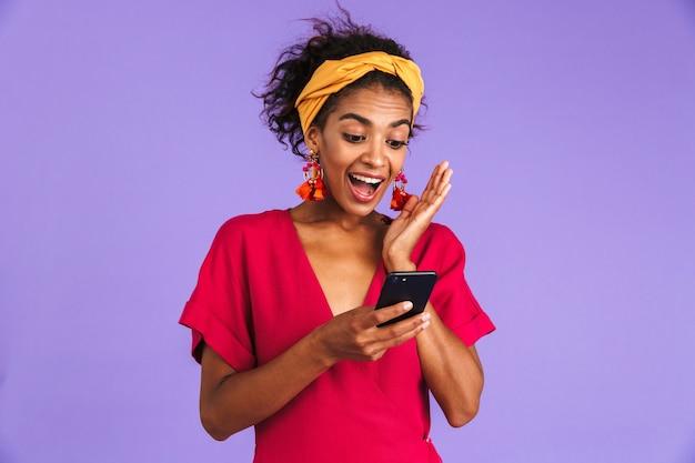 Mulher africana feliz surpresa num vestido usando smartphone e se alegra com a parede roxa Foto Premium