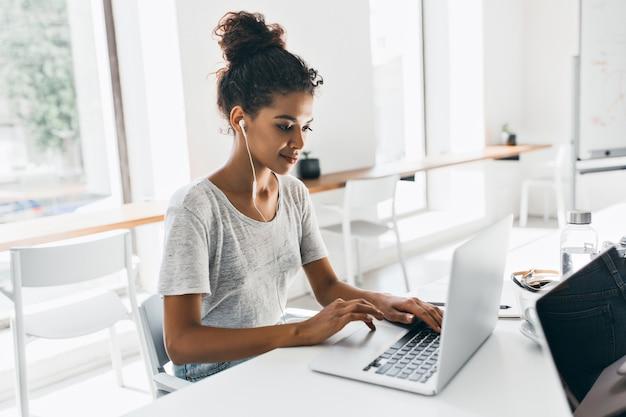 Mulher africana romântica com penteado da moda, sentado no local de trabalho e analisando dados. retrato interno da aluna negra trabalhando com o laptop antes do exame. Foto gratuita