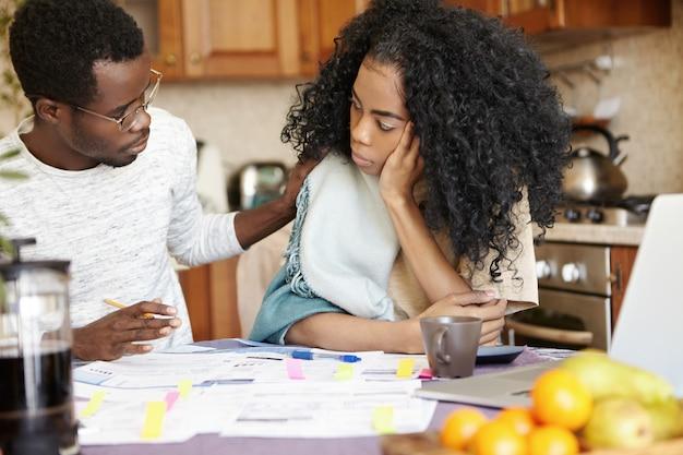 Mulher africana triste com penteado afro parecendo triste e infeliz por causa dos problemas financeiros da família, enquanto seu marido está sentado ao lado dela, tocando seu ombro, tentando animá-la Foto gratuita