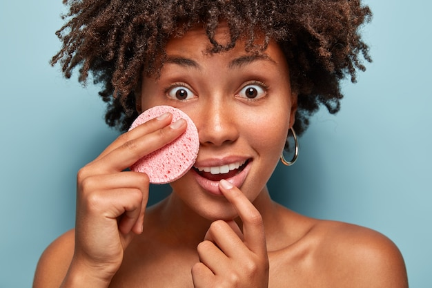 Mulher afro-americana alegre e surpresa ouve conselhos sobre como cuidar da pele, segura a esponja cosmética na bochecha, tem os olhos bem abertos, reação de choque, remove a maquiagem. conceito de spa e relaxamento Foto gratuita
