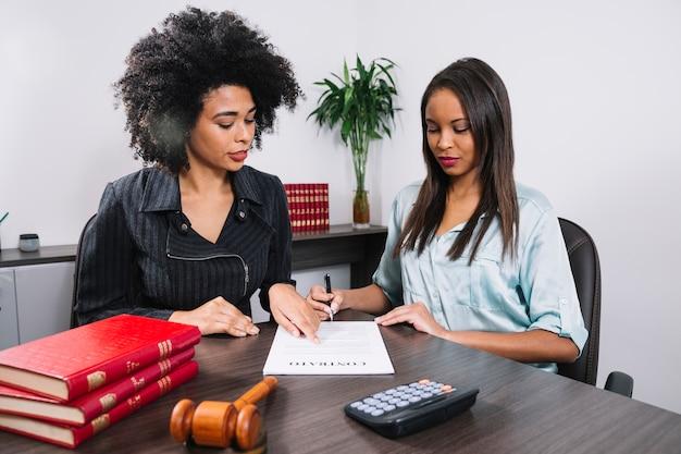 Mulher afro-americana, apontando para o documento perto de senhora com caneta na mesa Foto gratuita