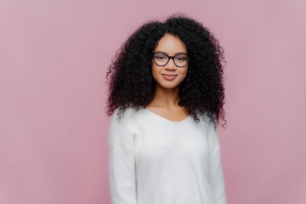 Mulher afro-americana atraente olha através de óculos transparentes Foto Premium