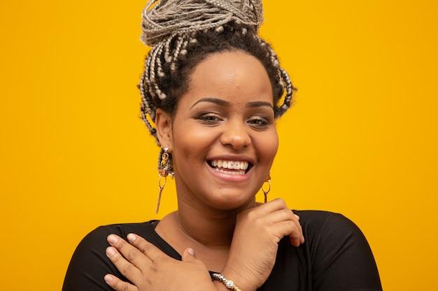 Mulher afro-americana bonita nova com cabelo do dread no amarelo Foto Premium