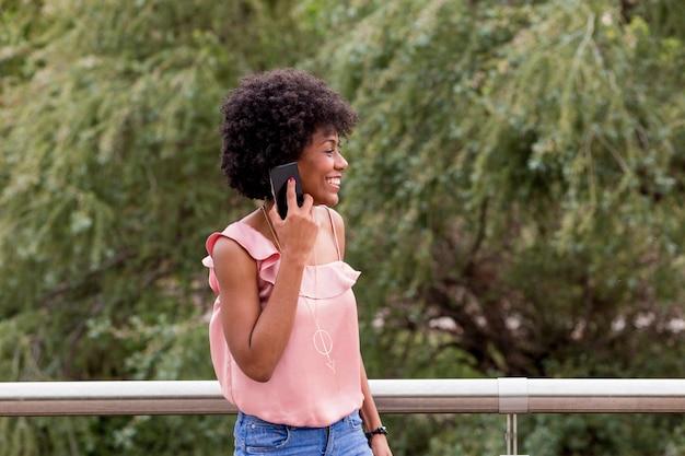 Mulher afro-americana bonita nova feliz que sorri e que usa o telefone móvel. fundo verde primavera ou verão. roupa casual ao ar livre Foto Premium
