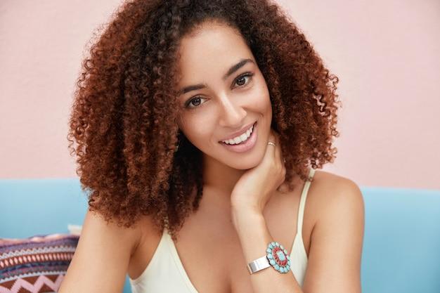 Mulher afro-americana com cabelos negros crespos, sorriso largo, satisfeita em passar as férias de verão em um resort rural Foto gratuita