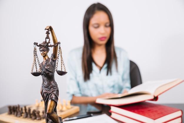 Mulher afro-americana com livro na mesa perto de xadrez, smartphone e estátua Foto Premium