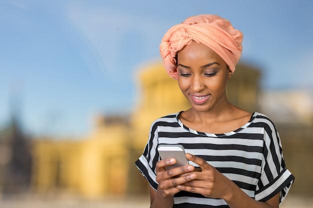 Mulher afro-americana com um telefone móvel Foto Premium