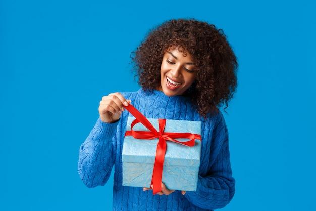 Mulher afro-americana curiosa e feliz, sorridente, garota do dia b de suéter de inverno, puxando o nó atual para desembrulhar o presente e ver o que dentro, comemorando o natal, feriados de ano novo, fundo azul Foto Premium