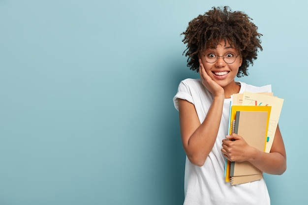 Mulher afro-americana de aparência agradável segura blocos de notas, papéis, estudos na faculdade, feliz por terminar os estudos Foto gratuita