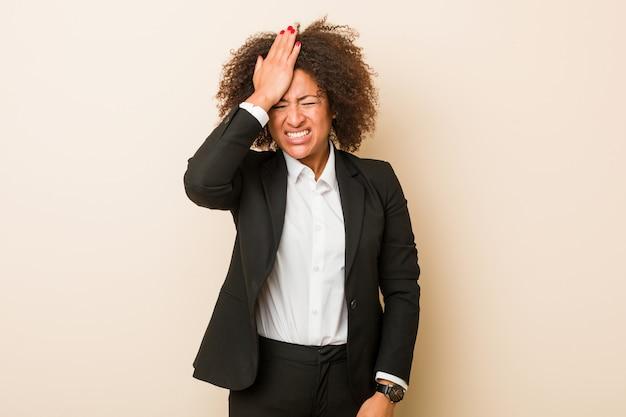 Mulher afro-americana de negócios jovem esquecendo algo, batendo na testa com a palma da mão e fechando os olhos. Foto Premium