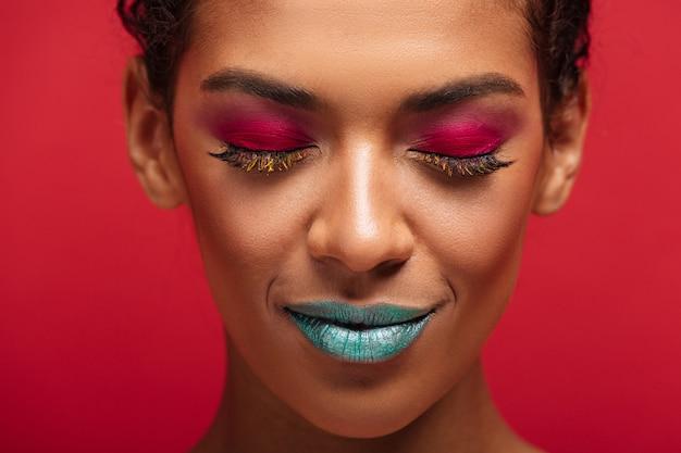 Mulher afro-americana encantadora de macro sendo elegante e moderno usando cosméticos coloridos posando com os olhos fechados, por cima do muro vermelho Foto gratuita