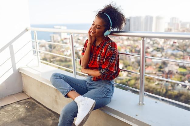 Mulher afro-americana feliz desfrutando de uma música adorável por fones de ouvido, vestida com camisa quadriculada, de pé no telhado. fundo de paisagem urbana. Foto gratuita