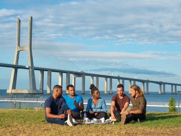 Mulher afro-americana focada falando com os amigos no gramado. jovem alegre em óculos e dreadlocks, comunicando-se com os colegas. conceito de comunicação Foto gratuita