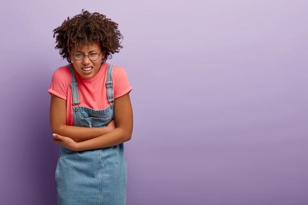 Mulher afro-americana insatisfeita segura as mãos na barriga, cerra os dentes por causa de sensações desagradáveis, tem distúrbios ou cólicas menstruais, sente desconforto na barriga, usa sarafan jeans. Foto gratuita