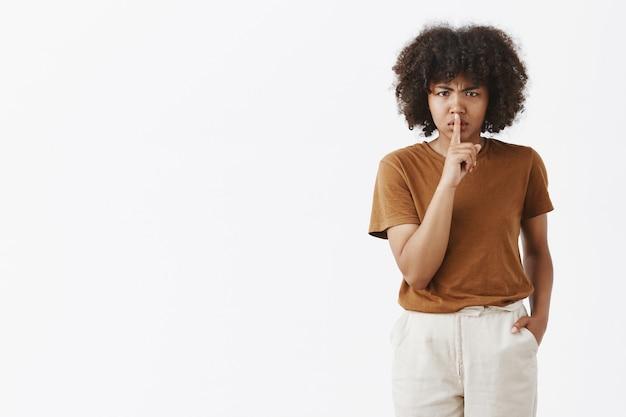Mulher afro-americana mandona e insatisfeita com penteado afro franzindo a testa por não gostar de dizer shh, mostrando um gesto de silêncio com o dedo indicador sobre a boca fechada Foto gratuita