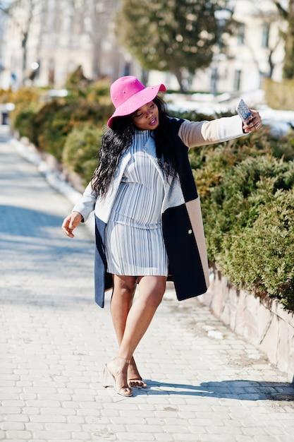 Mulher afro-americana no chapéu e casaco com telefone andando nas ruas. Foto Premium