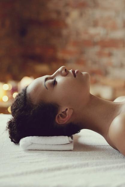 Mulher afro-americana, recebendo uma massagem relaxante no spa Foto gratuita